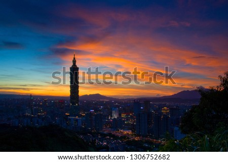 Taipei, Taiwan - August 6, 2008: Sunset moments, golden clouds and blue skies, brilliant lights of urban architecture. #1306752682