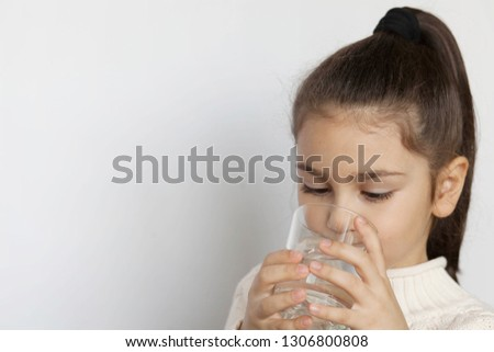 Cute child girl drinking water on white background. Pure water. #1306800808