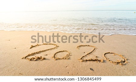 Happy New Year 2020  written on seashore sand at sunrise concept. coming concept sandy tropical ocean beach lettering concept image and the sea shore. Element of design. #1306845499