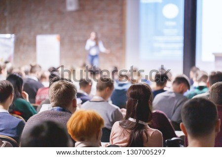 Adult students listen to professor's lecture in class room, hands up for queue of asking question to Lecturer or poll voting. Rear view, Audience Watching a Presentation. Business, education. #1307005297