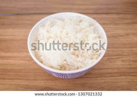 Rice cooked in a white cup placed on a wooden table, ready to serve #1307021332