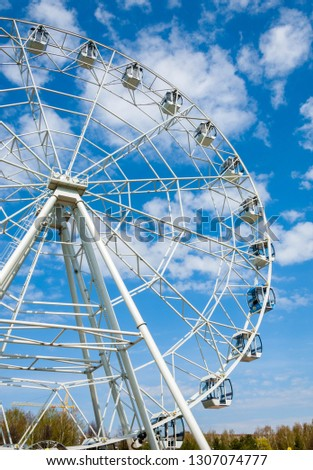 Ferris wheel an amusement-park or fairground ride consisting of a giant vertical revolving wheel with passenger cars suspended on its outer edge. #1307074777
