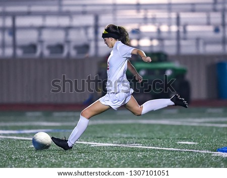 Young high school girl playing in a soccer match #1307101051