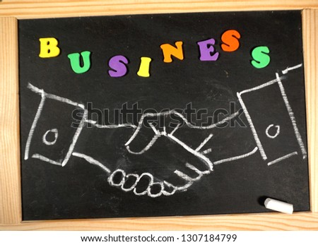 Business handshake on chalkboard with positive message                                #1307184799