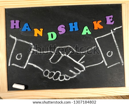 Business handshake on chalkboard with positive message                                #1307184802