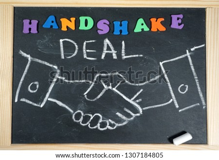 Business handshake on chalkboard with positive message                                #1307184805