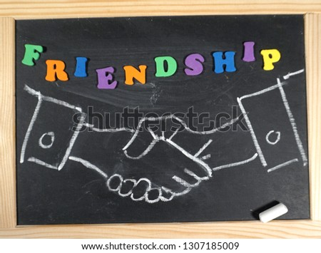 Friendship handshake message on chalkboard  #1307185009