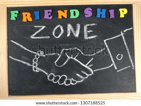 Friendship zone handshake on chalkboard                              #1307188525