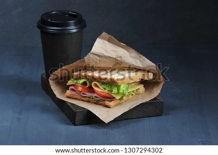 Sandwich with ham and cheese and paper cup with a drink on a dark background. Sandwich in a paper bag. Lettuce and tomato slices are used in the sandwich filling. The concept of fast food. Close-up. #1307294302