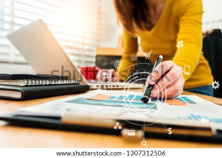business documents on office desk with laptop and smart phone and graph business diagram and women working at office . #1307312506