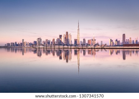 Beautiful colorful sunrise lighting up the skyline and the reflection of Dubai Downtown. Dubai, United Arab Emirates. #1307341570