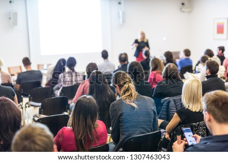 Business and entrepreneurship symposium. Female speaker giving a talk at business meeting. Audience in conference hall. Rear view of unrecognized participant in audience. Copy space on whitescreen. #1307463043