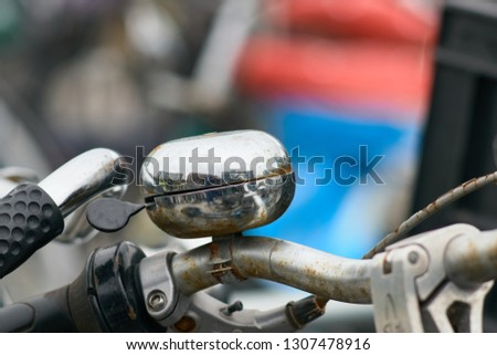 Close up of a rusty chromed steel bycicle bell mounted on the handle bar of an old bike. #1307478916