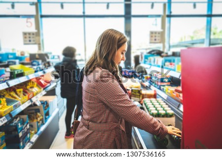 Woman at the supermarket in the box waiting in line to pay for her purchases. Girl about to pay for her products in the market #1307536165