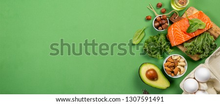 Keto diet concept - salmon, avocado, eggs, nuts and seeds, bright green background, top view #1307591491