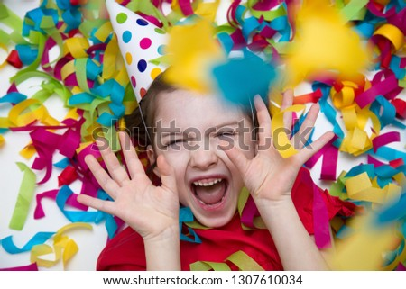 Birthday. A child in a red dress on a background of bright confetti celebrates a bright event. Have fun-image #1307610034