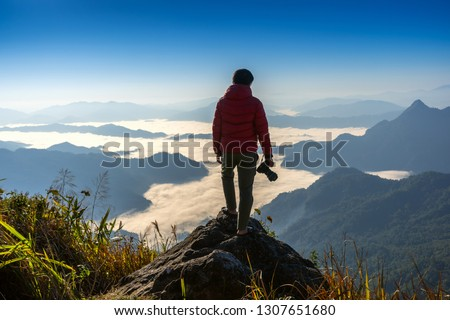 Photographer hand holding camera and standing on top of the rock in nature. Travel concept. #1307651680