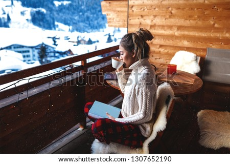Blonde with long hair and oversize sweater sitting on the bench covered with natural sheep fur, holding her favourite book and drinking tasty coffee with amazing aroma. Wooden furniture and walls.