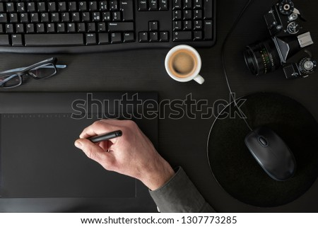 Designer drawing on graphic tablet on black desk #1307773285