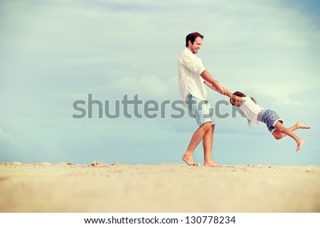 Healthy father and daughter playing together at the beach carefree happy fun smiling lifestyle #130778234