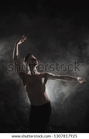A young male ballet dancer with black leggings and a naked torso performs dance moves against a gray grunge background, with a light of lights and smoke. Conceptual art of contemporary. #1307817925