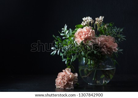 Carnations and pistachio sprigs in a glass vase with water, flower head next to the vase. #1307842900