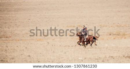Shymkent, Kazakhstan, November 5, 2018. Nomad riders train on horseback in the steppes of Kazakhstan. Kazakh traditions. Folk entertainment. Kazakh national game Kokpar.  #1307861230