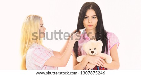 Sisters, best friends in pajamas making braid, hairdo each other. Ladies on smiling faces with plush toy bear look cute. Girls in pink pajamas, isolated white background. Girlish leisure concept. #1307875246