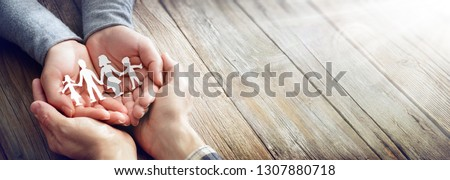 Family Care - Hands With Paper Silhouette On Table Royalty-Free Stock Photo #1307880718