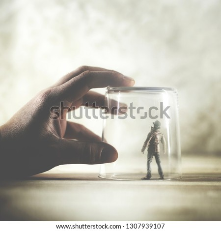little man trapped in a glass, surreal concept Royalty-Free Stock Photo #1307939107