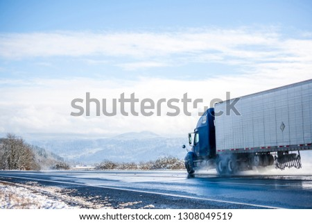 Big rig pro long haul blue semi truck tractor transporting commercial cargo in refrigerator semi trailer going on the wet glossy road with water from melting snow and winter snowy trees on the side #1308049519