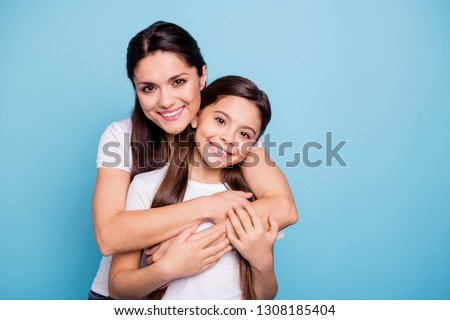 Close up photo amazing pretty two people brown haired mum mom small little daughter stand hugging piggy back lovely free time rejoice wearing white t-shirts isolated on bright blue background #1308185404