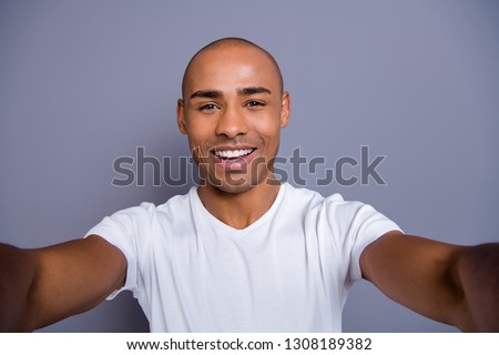 Close up photo healthy masculine dark skin he him his macho bald head arms telephone make take selfies cheerful wearing white t-shirt outfit clothes isolated grey background