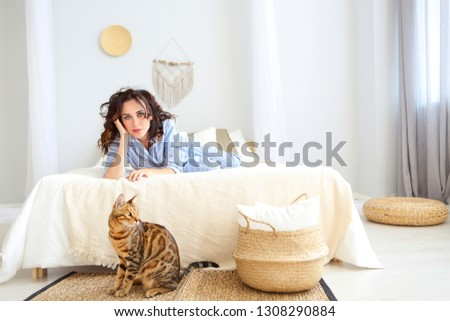 Portrait of attractive smiling woman in pajamas with bengal cat resting on bed at home  #1308290884