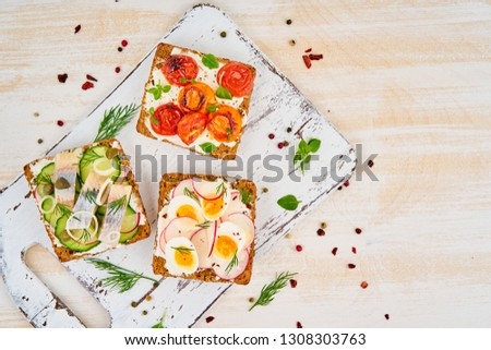 Smorrebrod - traditional Danish sandwiches. Black rye bread with herring, egg, tomatoes, radish on white wooden table, top view #1308303763