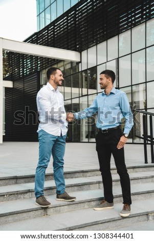 Young businessmen shaking hands in a modern company grounds. Smiling and talking about business. #1308344401