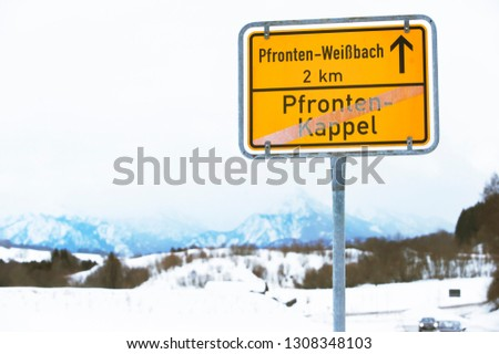 Yellow Traffic Sign with Local Town Names. Winter Landscape with Mountains on Background. Pfronten in Bavaria, Germany.