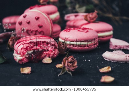 macaroons with raspberries and roses on a dark background #1308455995