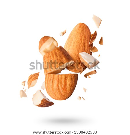 Flying in air fresh raw whole and cut almonds  isolated on white background. Concept of Almonds is torn to pieces close-up. High resolution image #1308482533