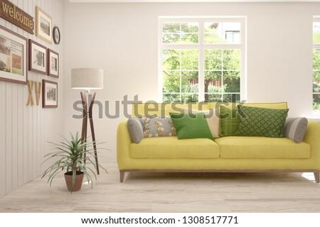 White stylish minimalist room with sofa and summer landscape in window. Scandinavian interior design. 3D illustration #1308517771