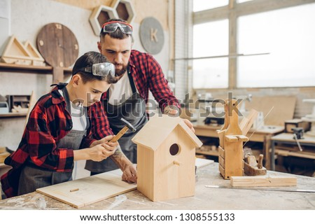 Carpenter building a wooden birdhouse together with his kid. A little son is participating actively in hand made process. Happy fatherhood and DIY concept. Royalty-Free Stock Photo #1308555133