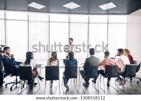 Achieving best results after annual refresher course. Indian young business mentor conducting a business training while standing in front of people sitting in row at meeting room. #1308558112