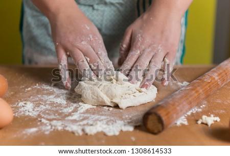 close up scene of female hands making dough #1308614533