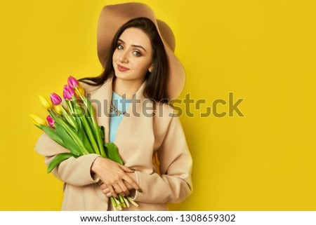Fashion photo of a beautiful young woman with tulips in her hand .she dressed in a beautiful coat,  and T-shirt with stripes on the yellow background .Spring concept. March 8. beautiful girl. #1308659302