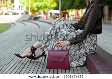 Fashionable young woman in high heel black shoes, black blouse, midi skirt with snake print and burgundy handbag in hand on the city street. Street style. #1308676651