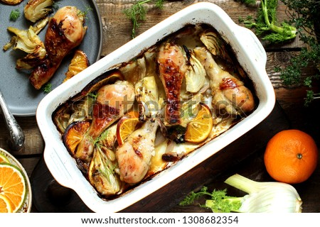 dish with fennel. Baked chicken drumsticks with fennel and oranges. festive dish, popular in the Mediterranean. Keto diet dish. ceramic baking dish. top view. Flatlay #1308682354