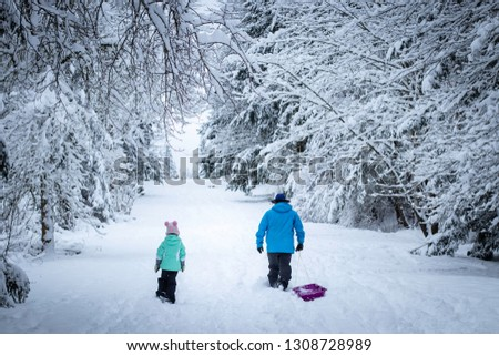 A dad pulls a sled alongside his daughter on a snowy trail in Washington State.  #1308728989
