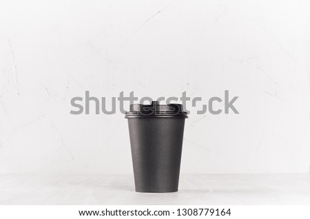 Coffee mockup -  blank black paper cup with cap on white wood table, coffee shop interior. Modern elegant concept for branding identity, advertising, design. #1308779164