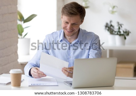 Millennial satisfied businessman sitting at the desk in office room holding paper document reading letter feels happy excited by great news. Employee getting salary raise or bonus from company boss #1308783706