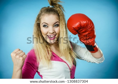 Funny blonde girl female boxer in big fun red gloves playing sports boxing studio shot on blue #1308837304